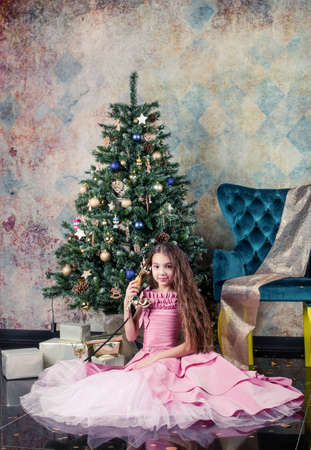girl with christmas tree. girl with long hair sits on a chair. Girl in a pink fluffy dress. Christmas photo session in the studio. call the old phone