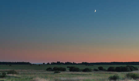 vespers: A sunset with a slice of moon still in the sky