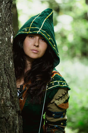 Staging photo of beautiful woman in fantasy suit with hood in forest Stock Photo