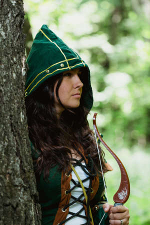 staging: Staging photo of beautiful woman in fantasy suit with hood in forest Stock Photo