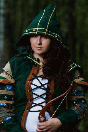 staging: Staging photo of beautiful woman in fantasy suit with hood and bow in forest