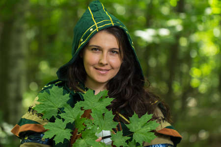 staging: Staging photo of beautiful woman in fantasy suit with hood and leafs in forest