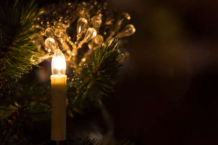 festive pine cones: Christmas toy candle in front of a Christmas tree with sparkling lights on dark background