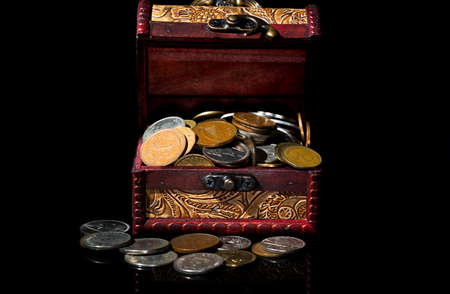 argent: old coins in chest on black background with reflections Stock Photo