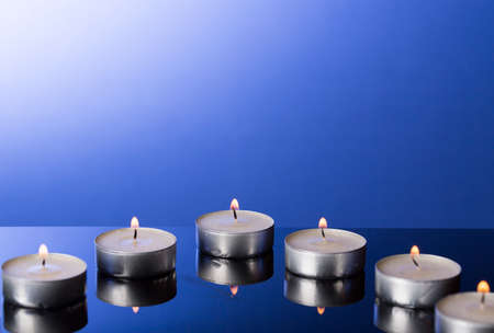 tea candles: Lit Tea Candles with Reflection on Blue background Stock Photo