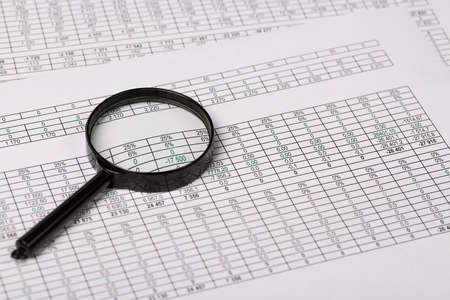 registros contables: Conceptual photo of Magnifying Glass on Reports with figures