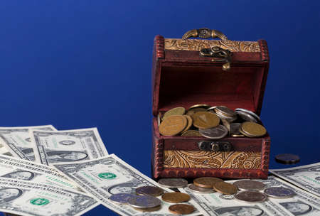 neologism: old coins in chest with dollar bills on blue background with reflections.