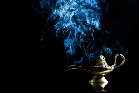 Lampada magica su sfondo nero della storia di Aladino con Genie che appaiono in blu concetto di fumo per aver voluto, la fortuna e la magia Archivio Fotografico - 61840773