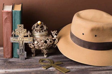 Adventure and archeological concept for lost artifacts with hat, vintage books, iron vase, key of life, vintage cross with brown background