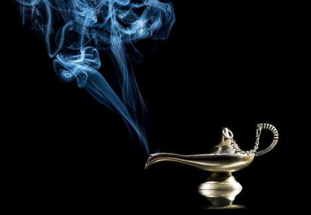 希望の場合は、運と魔法の青い煙コンセプトに現れる精霊とアラジンの物語から黒い背景に魔法のランプ。