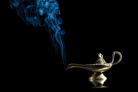abracadabra: Magic lamp on black background from the story of Aladdin with Genie appearing in blue smoke concept for wishing, luck and magic.