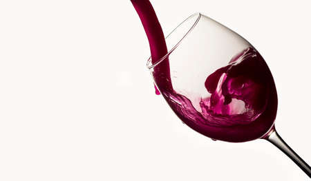 Red wine pouring in a wineglass on white background Stock Photo