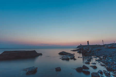 Lighthouse on the coast with stones during sunset.