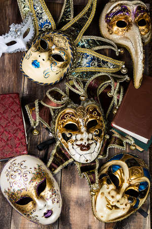 newsworthy: Venetian souvenir masks with vintage books on wooden surface. Stock Photo