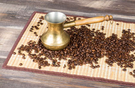coffeetree: Fresh coffee beans and gold coffee pot on wood table and bamboo cloth.