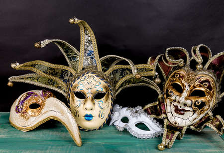 Maschere di carnevale veneziane sulla superficie verde di legno su sfondo scuro.