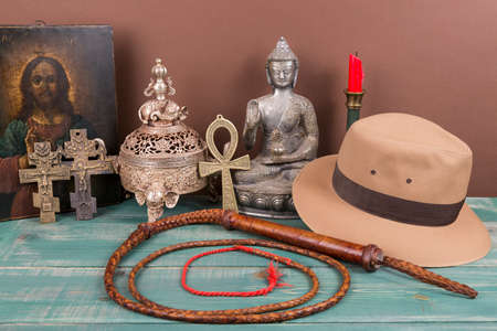 ankh cross: Adventure and archeological concept for lost artifacts with hat, whip, ancient iron vase, holy image, key of life, vintage crosses on green wood table and brown background. Stock Photo