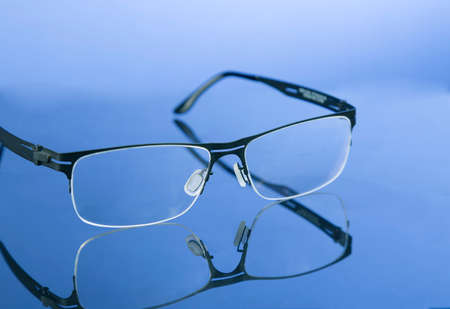 damaged roof: Reading moden eyeglasses on nice blue background with reflection.