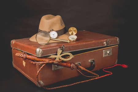 ankh: Travel and advanture concept. Vintage brown suitcase with clock, fedora hat, bullwhip, compass, magnifying glass and ankh key of life on dark background.