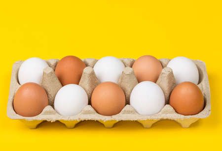 tolerancia: Tolerance concept. Brown eggs among white eggs in box on yellow background.