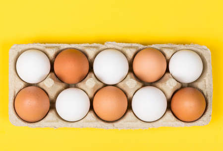 Tolerance concept. Brown eggs among white eggs in box on yellow background. Top view.