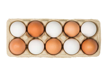 tolerancia: Tolerance concept. Brown eggs among white eggs in box isolated on white background. Top view. Foto de archivo