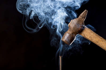 mastery: Abstract photo of metal rusty hammer above nail with smoke on black background. Stock Photo