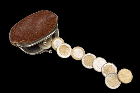 change purse: Vintage brown change purse and euro coins isolated on black background.