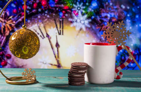 Christmas theme with toy ball, cookies and mug on green wooden surface against nice clock background. Stock Photo