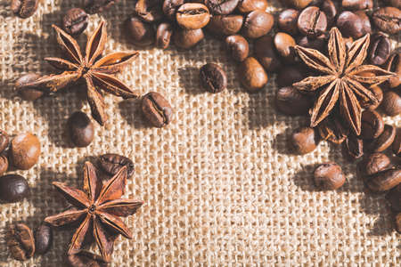 free space: Coffee beans on sackcloth with spices anise and free space for text Stock Photo