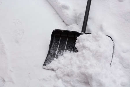 Snow cleaning concept. Black shovel and snow