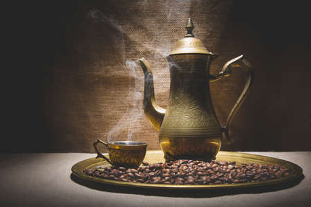 coffeepot: Vintage still life with heap of coffee beans near old copper coffeepot and cup with smoke on canvas background.