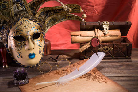 pluma de escribir antigua: Theater concept. Vintage still life with quill and scroll near mask, old chest and glasses on red background.