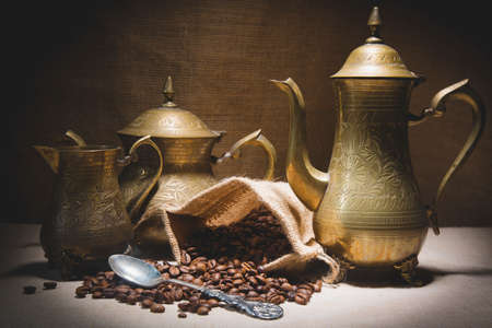 Heap of coffee beans in burlap sack with a vintage spoon and different vintage turkish coffeepots on canvas background. Stock Photo