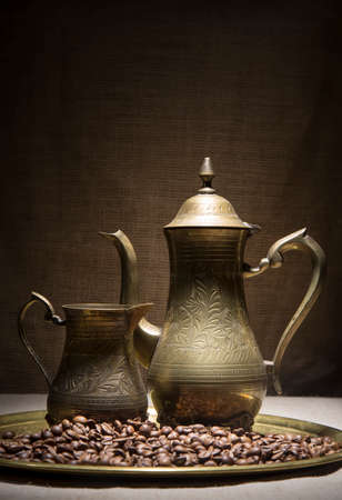 coffeepots: Vintage still life with heap of coffee beans near old copper coffeepots on bronze tray against canvas background.