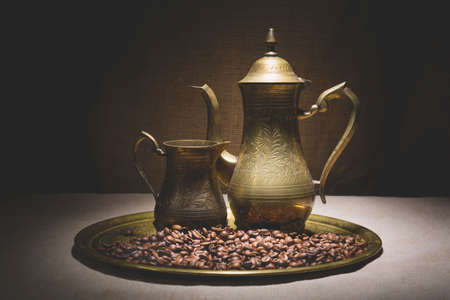 Vintage still life with heap of coffee beans near old copper coffeepots on bronze tray against canvas background.