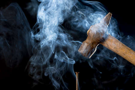 rusty nail: Hard work concept. Abstract photo of metal rusty hammer above nail with smoke on black background.