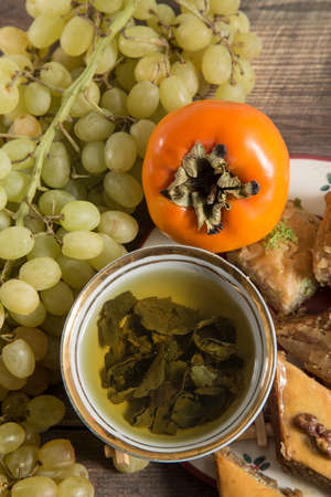 sweeties: Eastern breakfast. Green tea with sweeties, persimmon, grapes on wooden surface with free space.