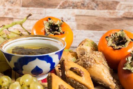 sweeties: Eastern breakfast. Green tea with sweeties, persimmons, grapes against stone background.