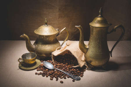 coffeepots: Heap of coffee beans in burlap sack with a vintage spoon and different vintage turkish coffeepots on canvas background. Stock Photo