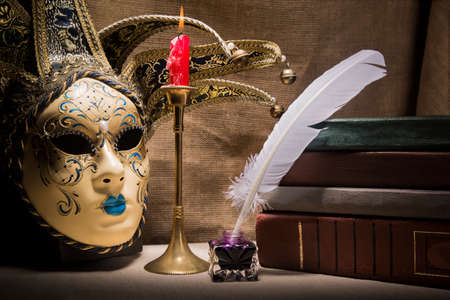 Vintage still life with old books near inkstand, feather, venezian mask and burning red candle in candlestick on canvas background.