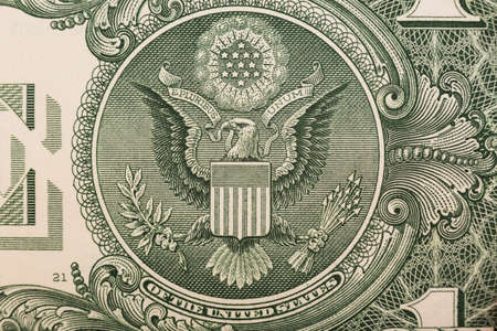 unum: A one dollar bill close up, showing the eagle on the great seal of the United States.