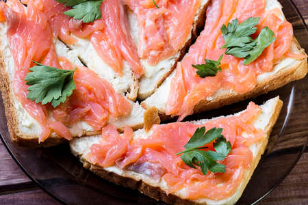 Sandwich wit salmon, butter and herb on a wooden board.
