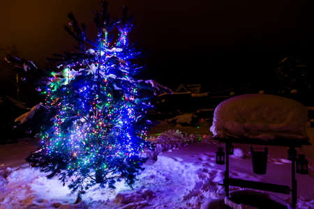 Decorated christmas tree outside with lights covered with snow. Stock Photo