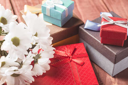 georgina: White chrysanthemum flowers with gift boxes on wooden table. Holiday card. Stock Photo