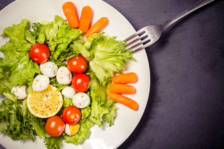Tasty salad with cherry tomatoes, salad leaves, lemon, spices, carrot and quail eggs on stone table with fork. Top view