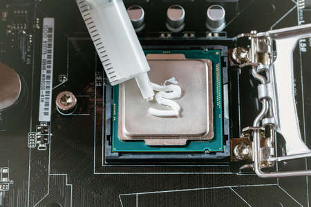 Applying thermal paste during CPU installation close up in the motherboard
