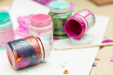 Different colorful paints and brush on white paper. Selective focus. Stock Photo