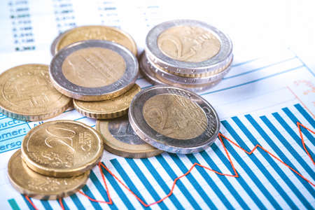 Euro coins on fluctuating graph. Selective focus.