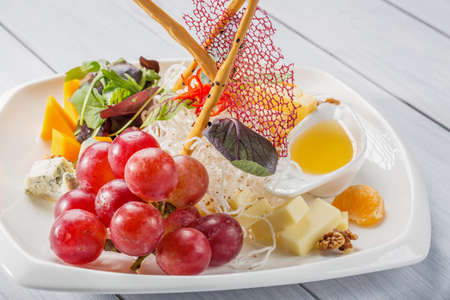 Restaurant cheese plate - various types of cheeses with grapes walnut and sauce on white & Restaurant Cheese Plate - Various Types Of Cheeses With Grapes ...